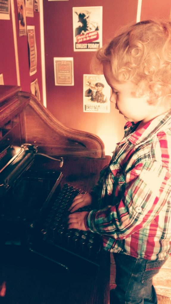 3 year old using an old typewriter at Gloucester Life Museum