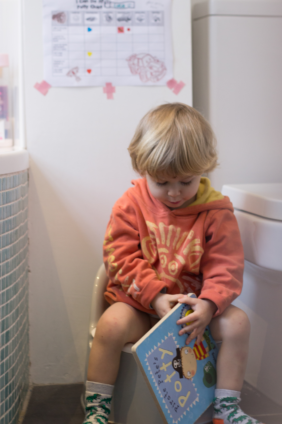 Toddler reading 'Pirate Pete's potty' book sat on the potty - nipitinthebud.co.uk